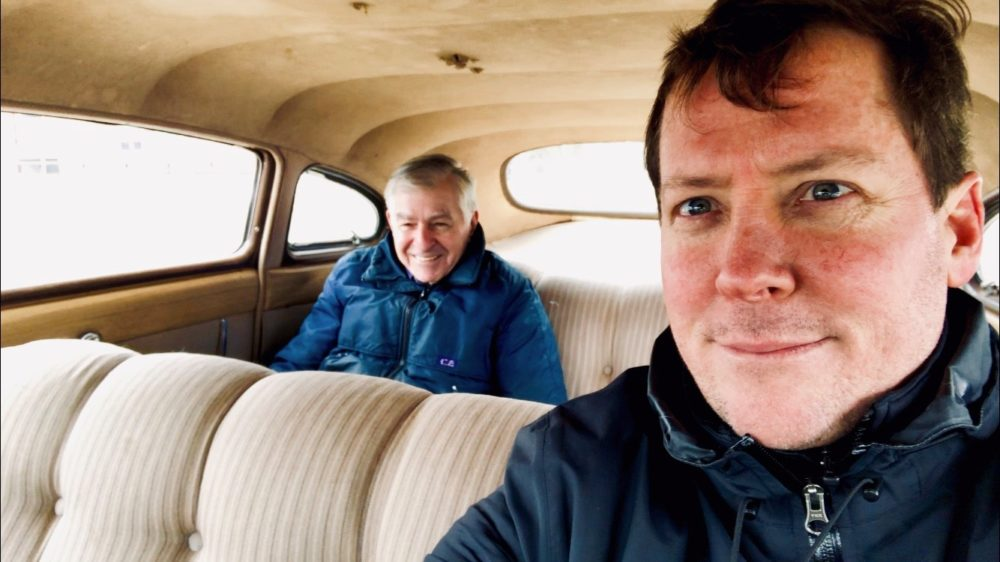 The author, Dan McNichol, is pictured with Governor Dukakis, who is riding in the back of his car. (Courtesy)