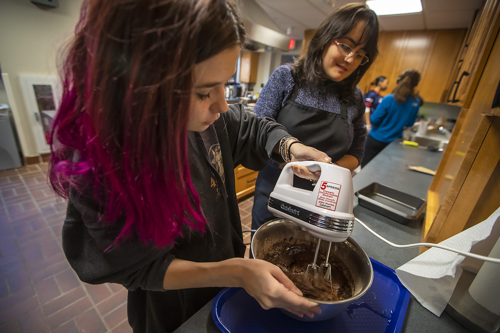 Maddy Baldwin uses a hand mixer to mix brownie dough as fellow student Sofia Causa Dumay assists. They are making brownies for the Super Bowl watch party. (Jesse Costa/WBUR)
