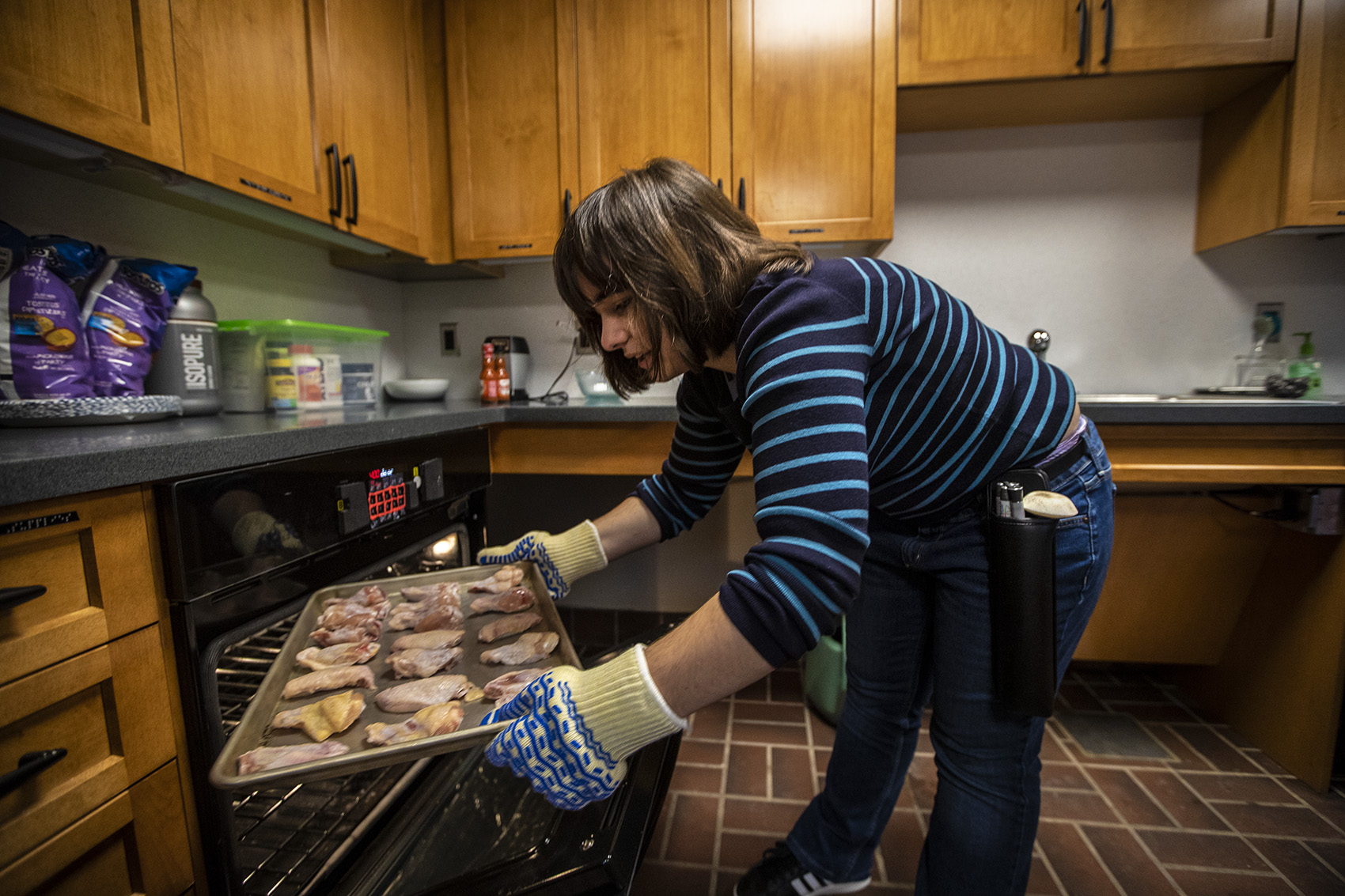 Haley Valente places the pan of chicken wings into the oven. (Jesse Costa/WBUR)