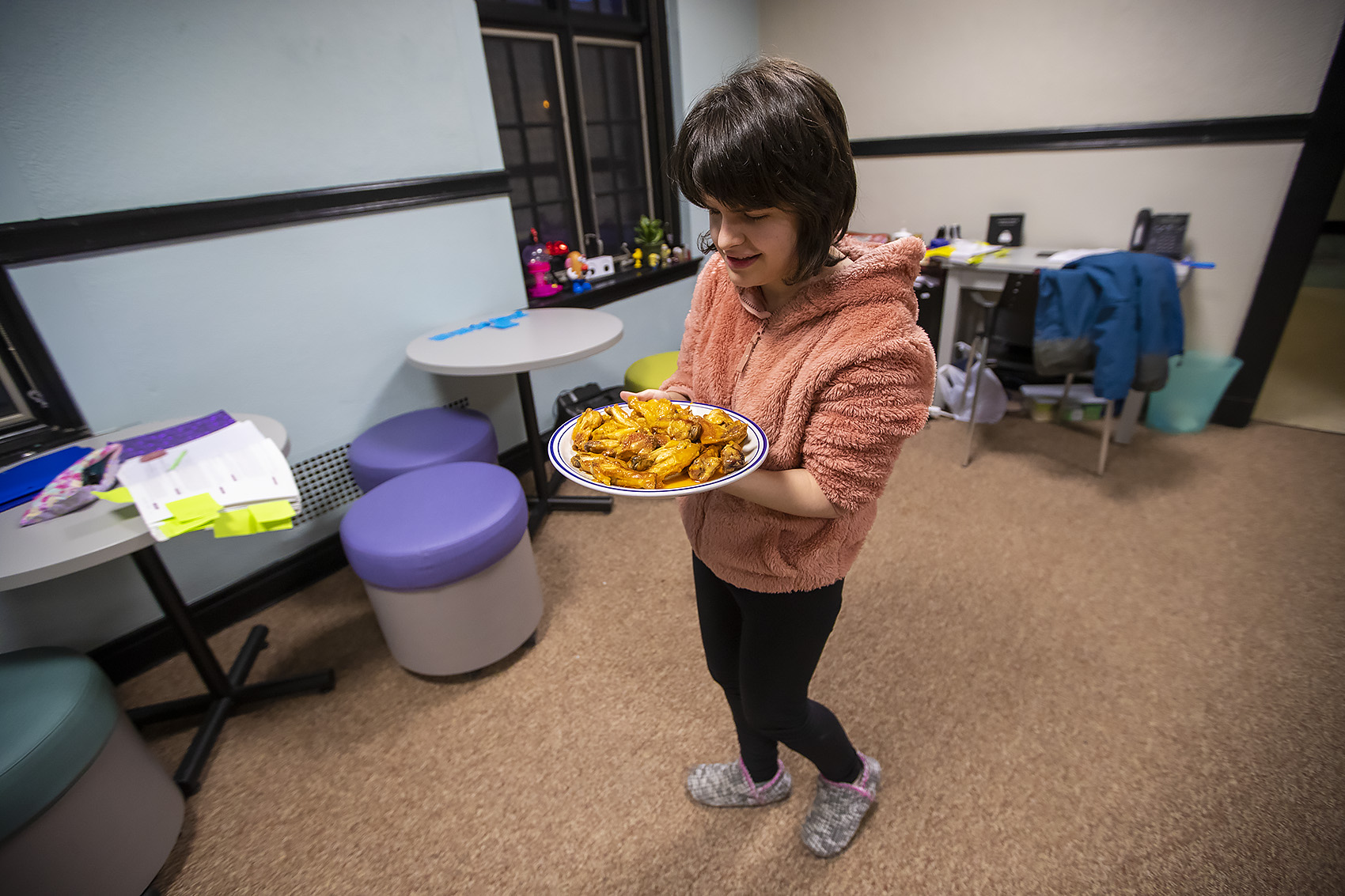 Jordan Scheffer brings the finished buffalo wings into the living room where the students will serve the food and watch the game. (Jesse Costa/WBUR)