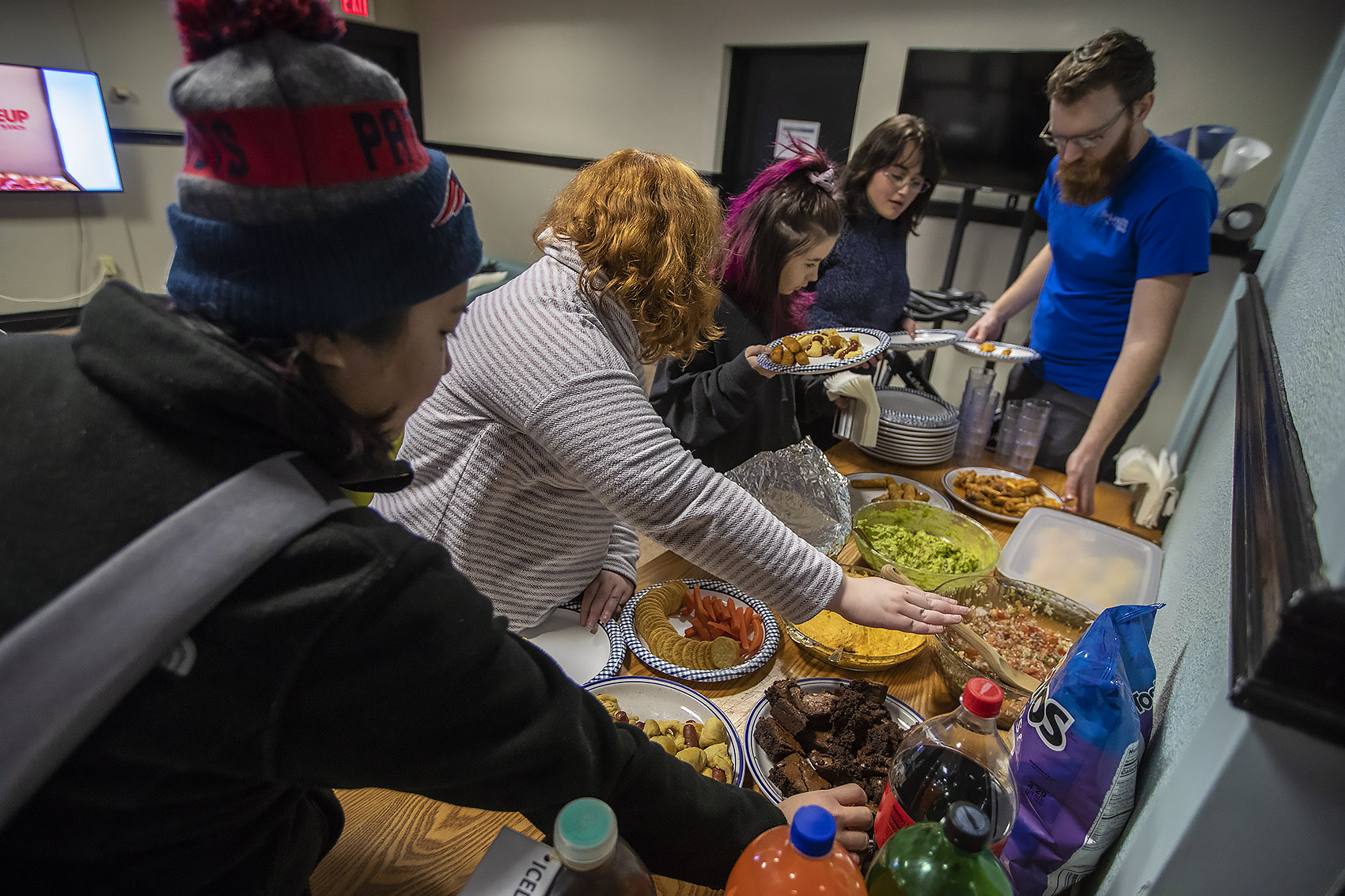 Everyone begins to dig into the food they prepared before the game begins. (Jesse Costa/WBUR)
