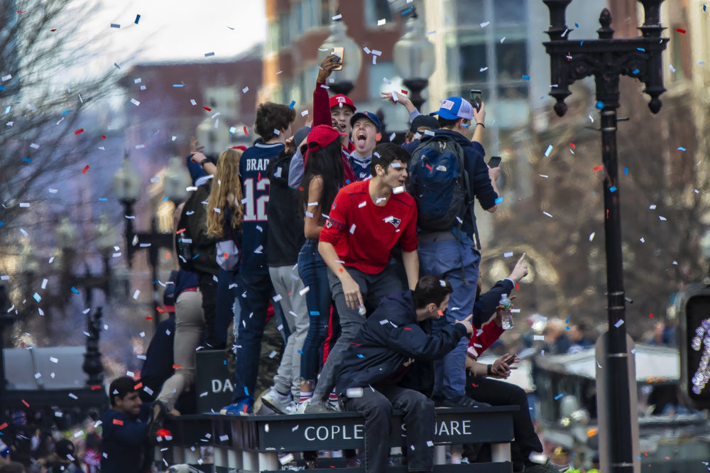 Patriots fans climbed up onto a bus shelter on Boylston St. to get a better position to see the parade. They were promptly told by police to get down. (Jesse Costa/WBUR)
