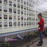 A boy stands as he looks at a photo of his father at memorial wall with photos of servicemen killed in the conflict with pro-Russian separatists in the country's east, in Kiev, Ukraine in 2017. (Efrem Lukatsky/AP)