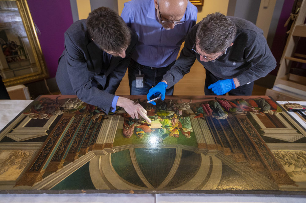 """Isabella Stewart Gardner Museum's William and Lia Poorvu Curator of the Collection Nathaniel Silver, Chief Conservator Gianfranco Pocobene and Accademia Carrara Museum curator Giovanni Valagussa inspect the Botticelli's """"The Story of Virginia."""" (Jesse Costa/WBUR)"""