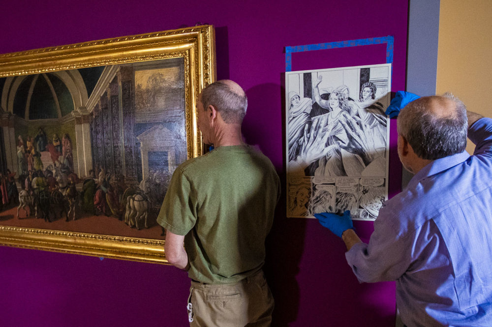 """Preparators at the Isabella Stewart Gardner Museum hang """"The Story of Virginia."""" Next to the painting, a preparator adjusts a drawing by award-winning graphic novelist Karl Stevens, who reimagined the paintings in a contemporary idiom: the cartoon (Jesse Costa/WBUR)"""