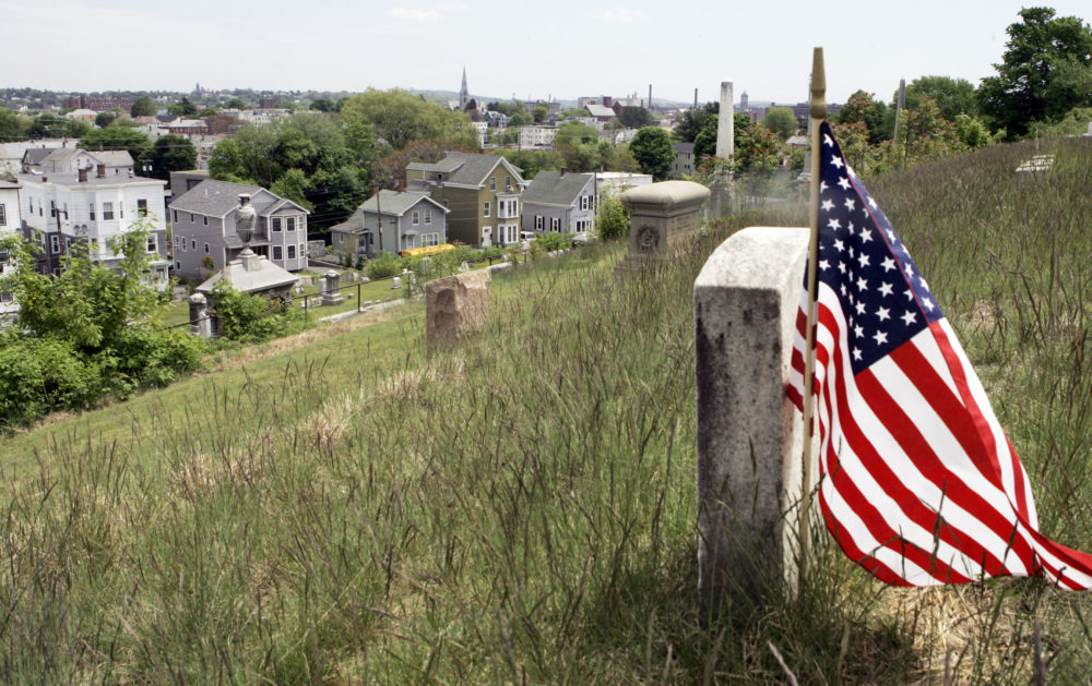 An U.S. flag is planted at a gravestone in Bellevue Cemetery in Lawrence, Mass. in 2007. (Elise Amendola/AP)