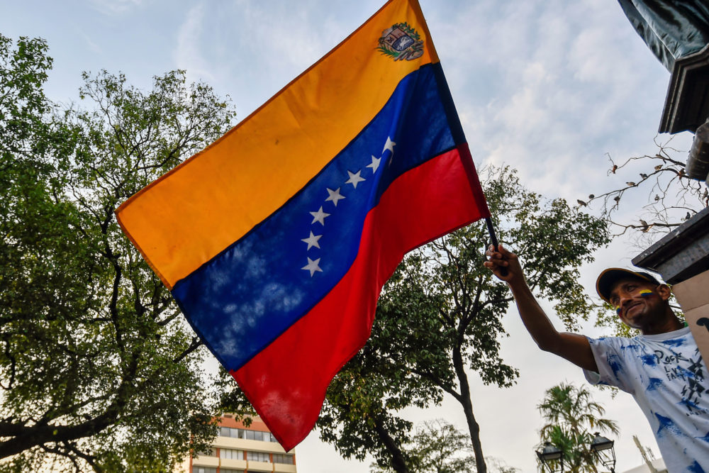 A Venezuelan holds a national flag during a protest against the government of President Nicolas Maduro at Santander square in Cucuta, Colombia, on the border with Venezuela, on Feb. 12, 2019. (Luis Robayo/AFP/Getty Images)