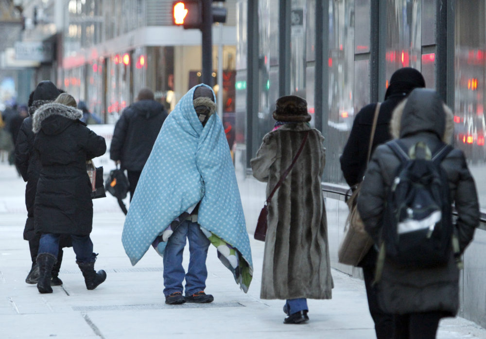 A homeless man who did not give his name bundles up in blankets in downtown Chicago during a deep freeze. (Kiichiro Sato/AP)