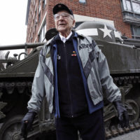 World War II tank gunner Clarence Smoyer poses for a portrait near the Charlestown Naval Shipyard in Boston, Feb. 20, 2019. The 95-year-old veteran was surprised with a ride through the streets of Boston in a Sherman tank, one of the tanks most widely used by the U.S. during the war. (Charles Krupa/AP)