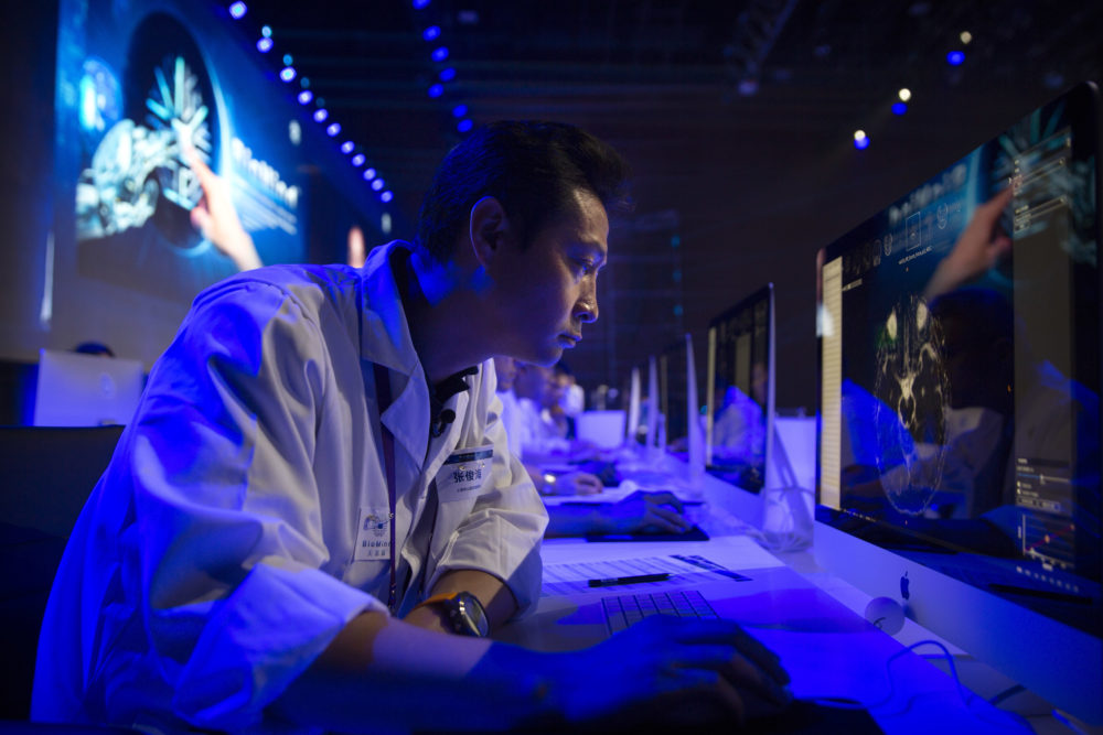 A doctor examines a magnetic resonance image of a human brain during the CHAIN Cup at the China National Convention Center in Beijing, June 30, 2018. A computer running artificial intelligence software defeated two teams of human doctors in accurately recognizing maladies in magnetic resonance images on Saturday, in a contest that was billed as the world's first competition in neuroimaging between AI and human experts. (Mark Schiefelbein/AP)