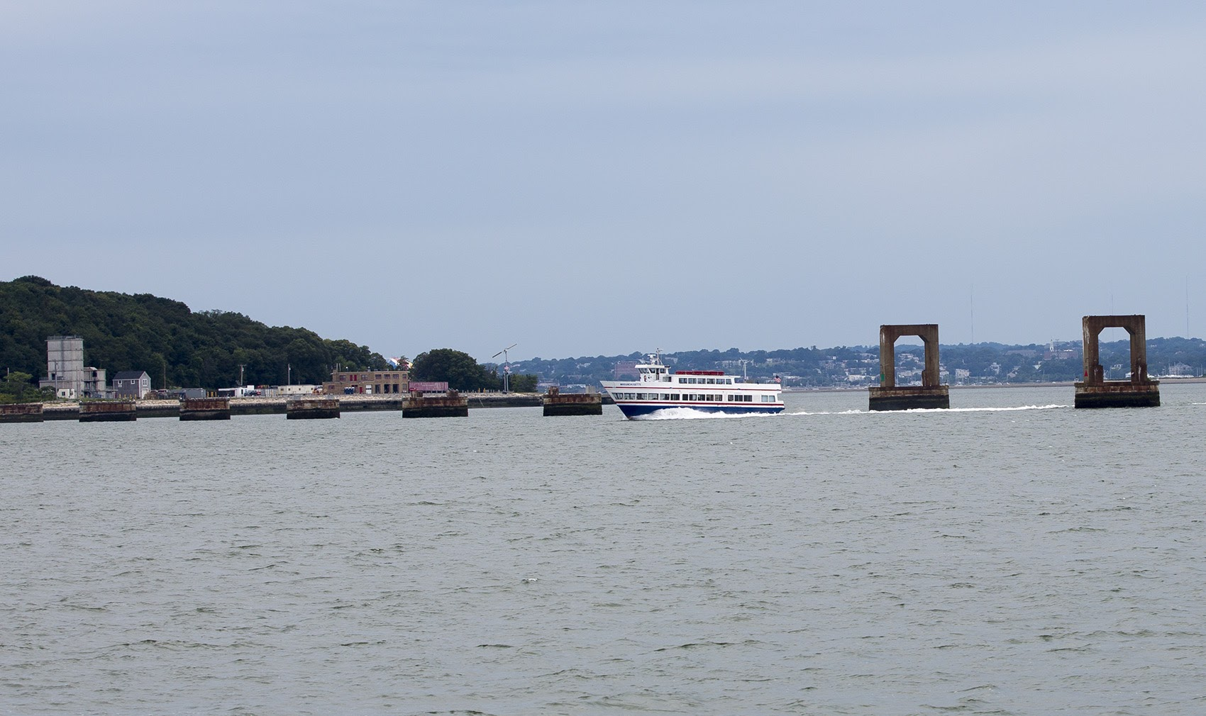 A ferry boat passes through the remnants of the Long Island Bridge in Boston Harbor in 2017. (Jesse Costa/WBUR)