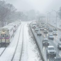 A commuter rail train and vehicles on the Mass. Turnpike make their way through light snow during the morning commute. (Robin Lubbock/WBUR)