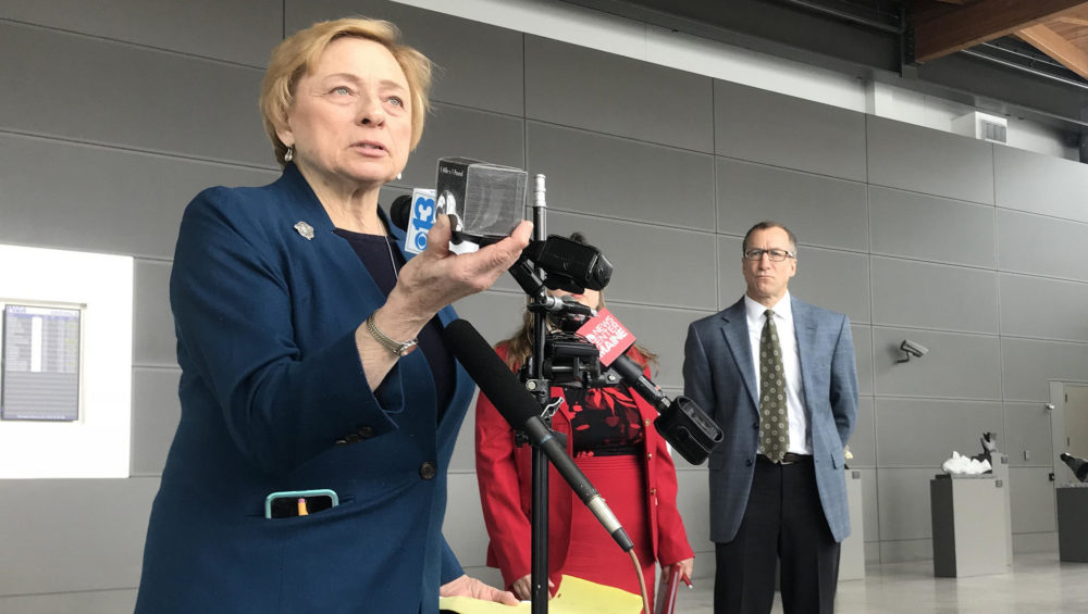 Maine Gov. Janet Mills holds up a pound of carbon at a press conference at the Portland Jetport on Thursday. (Fred Bever/Maine Public)