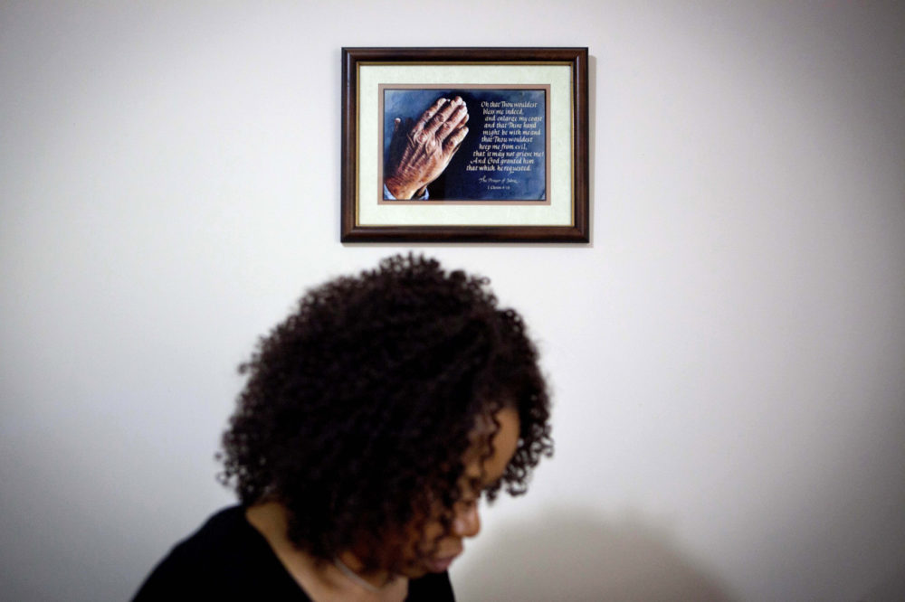 A prayer in a frame hangs on the wall as Patricia Jackson sifts through bank documents in her home Saturday, June 16, 2012, in Marietta, Ga. (David Goldman/AP)