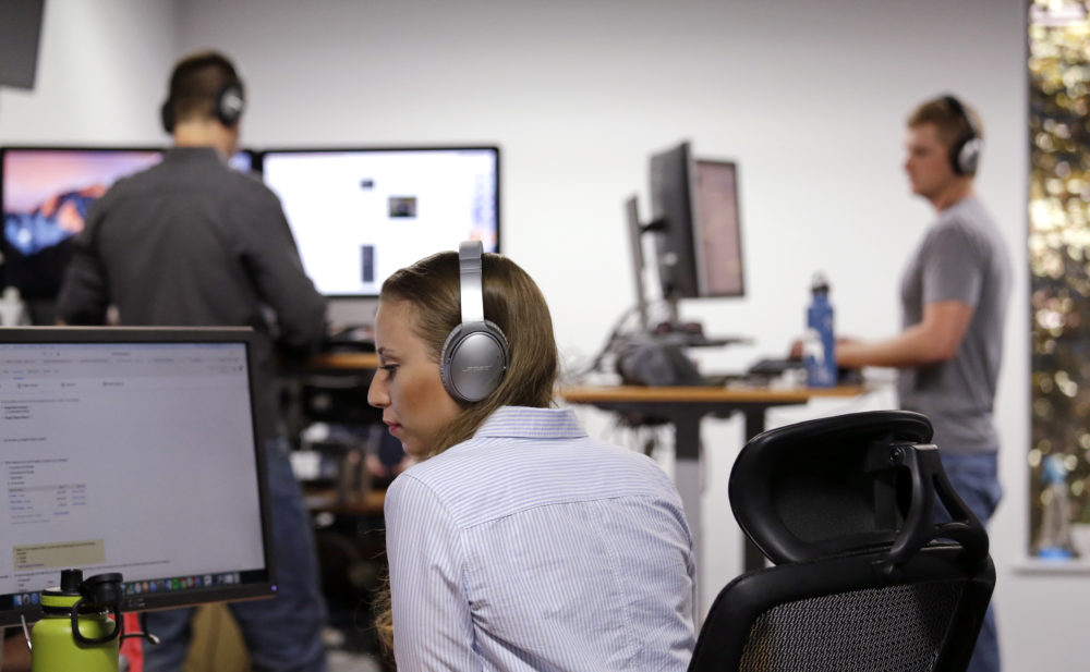 Meg Dowaliby, along with her colleagues behind, wears Bose noise-canceling headphones, a perk of her job, as she works at her computer at Geniuslink in Seattle. (Elaine Thompson/AP)