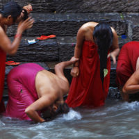 In this Sept. 10, 2013 file photo, Nepalese Hindu women bathe in the Bagmati River on Rishi Panchami, a day when rituals are performed to wash away sins committed during menstruation period, a period considered impure, in Katmandu, Nepal. Many menstruating women are still forced to leave their homes and take shelter in unhygienic or insecure huts or cow sheds until their cycle ends, though the practice, called Chhaupadi, was actually outlawed a decade ago. (Niranjan Shrestha/AP)