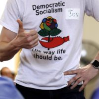 Jon Torsch, center, wears a T-shirt promoting democratic socialism during a gathering of the Southern Maine Democratic Socialists of America at City Hall in Portland, Maine, Monday, July 16, 2018. On the ground in dozens of states, there is new evidence that democratic socialism is taking hold as a significant force in Democratic politics. (Charles Krupa/AP)