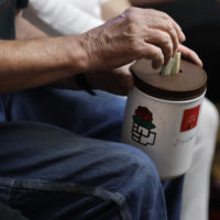 A patron puts a bill in a donation bucket, which features a red rose symbol, during a meeting of members of the Southern Maine Democratic Socialists of America in Portland, Maine, Monday, July 16, 2018. (Charles Krupa/AP)