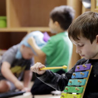 Elliott O'Neil plays on a xylophone at the Wallingford Child Care Center in Seattle. (Elaine Thompson/AP)