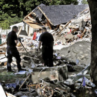 Fire investigators outside a home that exploded after the gas line failure on Sept. 13 in Lawrence. (Charles Krupa/AP)