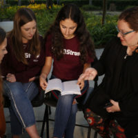 "In this Wednesday, Jan. 16, 2019 photo, Brianna Jesionowski, from far left to right, Brianna Fisher and Leni Steinhardt sit during an interview, as journalism teacher Sarah Lerner, right, makes a point regarding the new book called ""Parkland Speaks: Survivors from Marjory Stoneman Douglas Share Their Stories."" Students and teachers from the Florida school, where 17 died in  Feb. 2018 mass shooting, wrote the raw, poignant book about living through the tragedy. (Brynn Anderson/AP)"