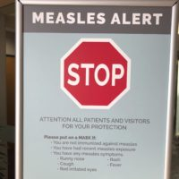 Signs posted at The Vancouver Clinic in Vancouver, Wash., warn patients and visitors of a measles outbreak on Wednesday, Jan. 30, 2019. The outbreak has sickened 39 people in the Pacific Northwest, with 13 more cases suspected. At least one patient who was sick with the measles has come to this clinic for treatment since the outbreak began Jan. 1, 2019. (AP Photo/Gillian Flaccus)