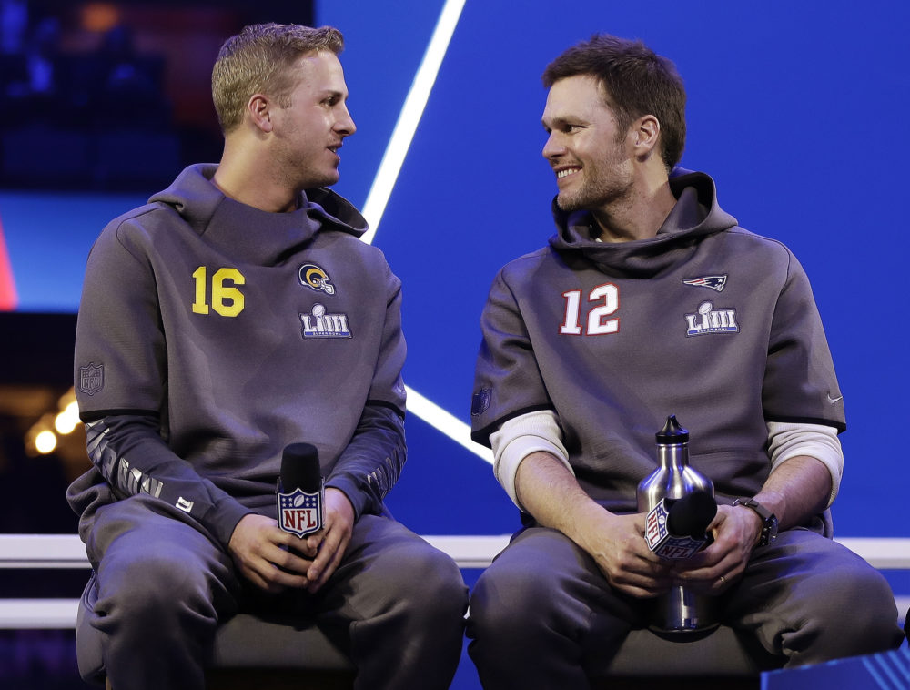 Los Angeles Rams' Jared Goff talks to New England Patriots' Tom Brady during Opening Night for the NFL Super Bowl 53 football game in Atlanta. The wide-eyed, talented Goff will try to lead his Rams past the grizzled, 41-year-old Brady, who is looking to guide the Patriots to their sixth Super Bowl victory.   (Matt Rourke/AP)