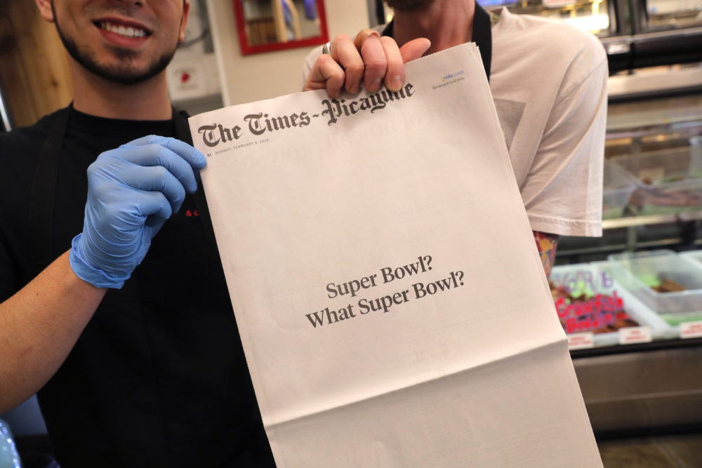 """Brothers Damien Hanford, right, and Matthew Hanford, hold their copy of the mostly blank front page of the New Orleans Times-Picayune newspaper, at Bergeron Boudin and Cajun Meats, in Harahan, La., Monday, Feb. 4, 2019. The newspaper's nearly blank front page summarized what those in the Big Easy think of the New England Patriots' win over the Rams on Sunday: """"Super Bowl? What Super Bowl?"""" (Gerald Herbert/AP)"""