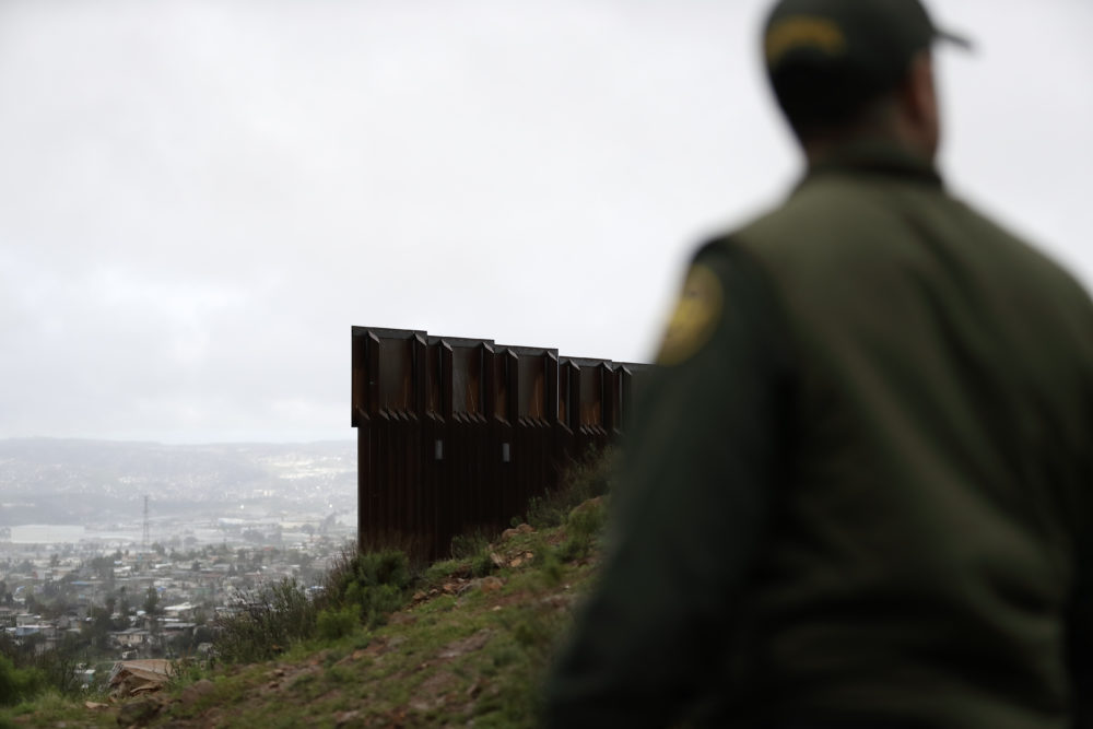 Border Patrol agent Vincent Pirro stands near where the border wall ends that separates Tijuana, Mexico, left, from San Diego, Tuesday, Feb. 5, 2019, in San Diego. (Gregory Bull/AP)