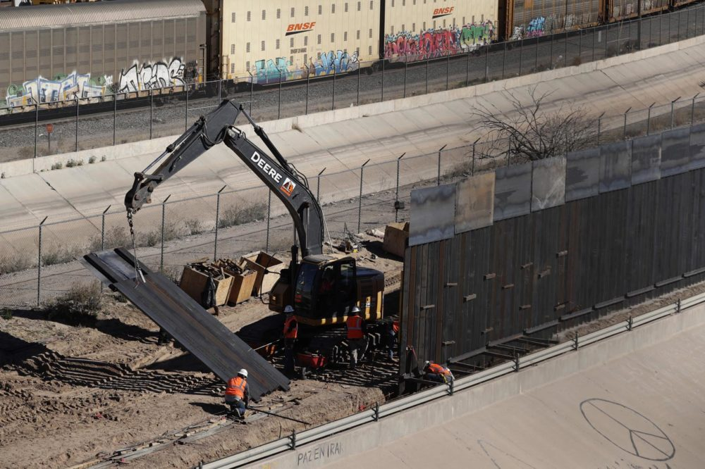 In this Tuesday, Jan. 22, 2019, photo, workers place sections of metal wall as a new barrier is built along the Texas-Mexico border near downtown El Paso. Such barriers have been a part of El Paso for decades and are currently being expanded, even as the fight over President Donald Trump's desire to wall off the entire U.S.-Mexico border. (Eric Gay/AP)