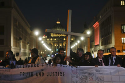 Survivors of sex abuse hold a cross as they gather in front of Via della Conciliazione, the road leading to St. Peter's Square, during a twilight vigil prayer of the victims of sex abuse, in Rome, Thursday, Feb. 21, 2019. (Gregorio Borgia/AP)