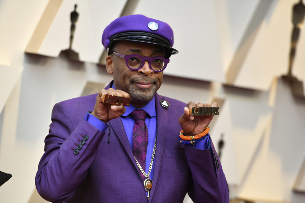 "Spike Lee holds up brass knuckles reading ""hate"" and ""love"" from his iconic film ""Do The Right Thing."" (Jordan Strauss/Invision/AP)"