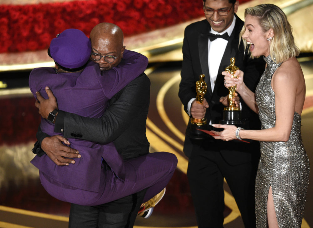 "Spike Lee jumps into Samuel L. Jackson's arms after he wins an Oscar for best adapted screenplay for ""BlacKkKlansman."" (Chris Pizzello/Invision/AP)"