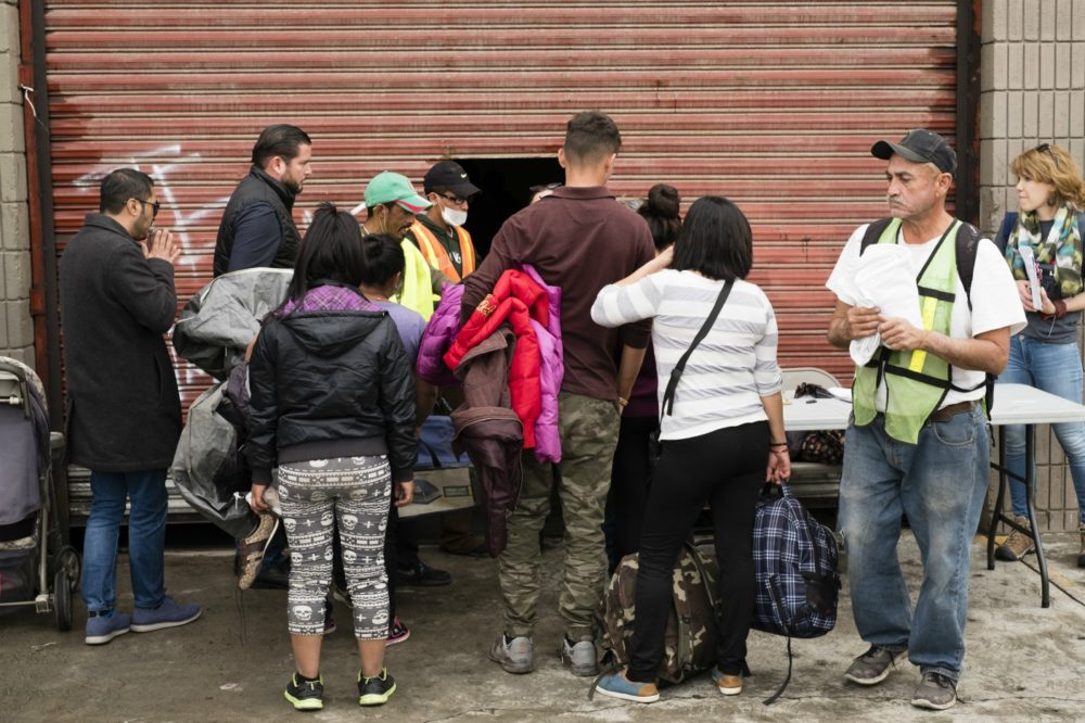 Migrants move their belongings into a temporary shelter provided by the Mexican government. The shelter is an old warehouse, without any running water or bathrooms. Co-author Karen Pita Loor is pictured behind the table, on the right. (Courtesy Jozef Staska)