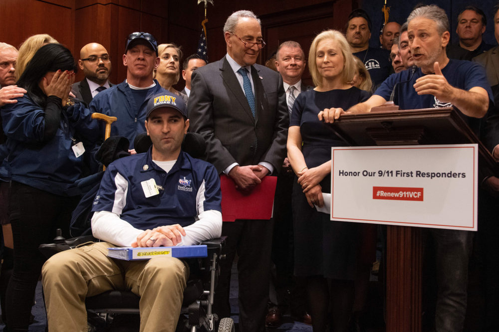 "Former ""Daily Show"" host Jon Stewart (right) with Senate Minority Leader Chuck Schumer (center), D-N.Y., Sen. Kirsten Gillibrand (second right), D-N.Y., and 9/11 first responders, survivors and their families to discuss the introduction of the bipartisan ""Never Forget the Heroes: Permanent Authorization of the September 11th Victim Compensation Fund Act."" (Jim Watson/AFP/Getty Images)"