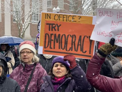 """More than 100 people protested at a """"Presidents Day Protest to Fight Trump's fake Crisis and Racist Deportation Forces,"""" on Monday, Feb. 18, 2019. (Simón Rios/WBUR)"""