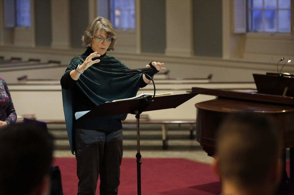 Amelia LeClair, director of Cappella Clausura, conducts a rehearsal at the Eliot Church in Newton.  (Hadley Green for WBUR)