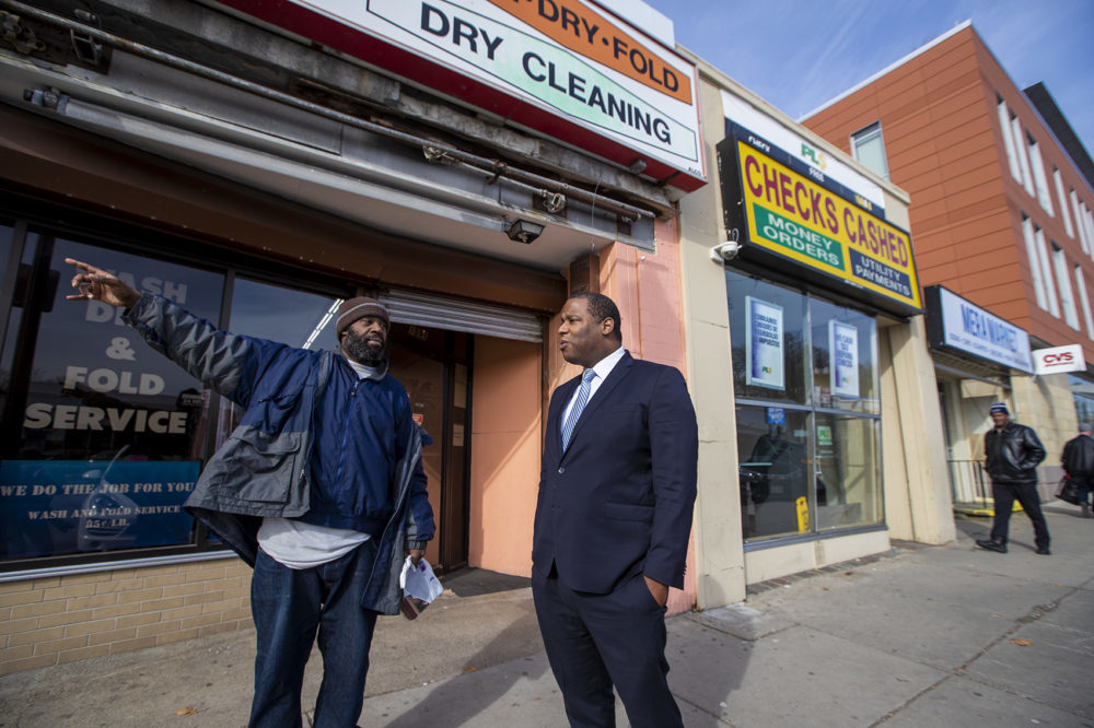 Rodney Weaver, left, speaks with former Boston City Councilor Tito Jackson about the prospect of jobs at the marijuana dispensary Jackson wants to open at this site in Mattapan Square. (Jesse Costa/WBUR)