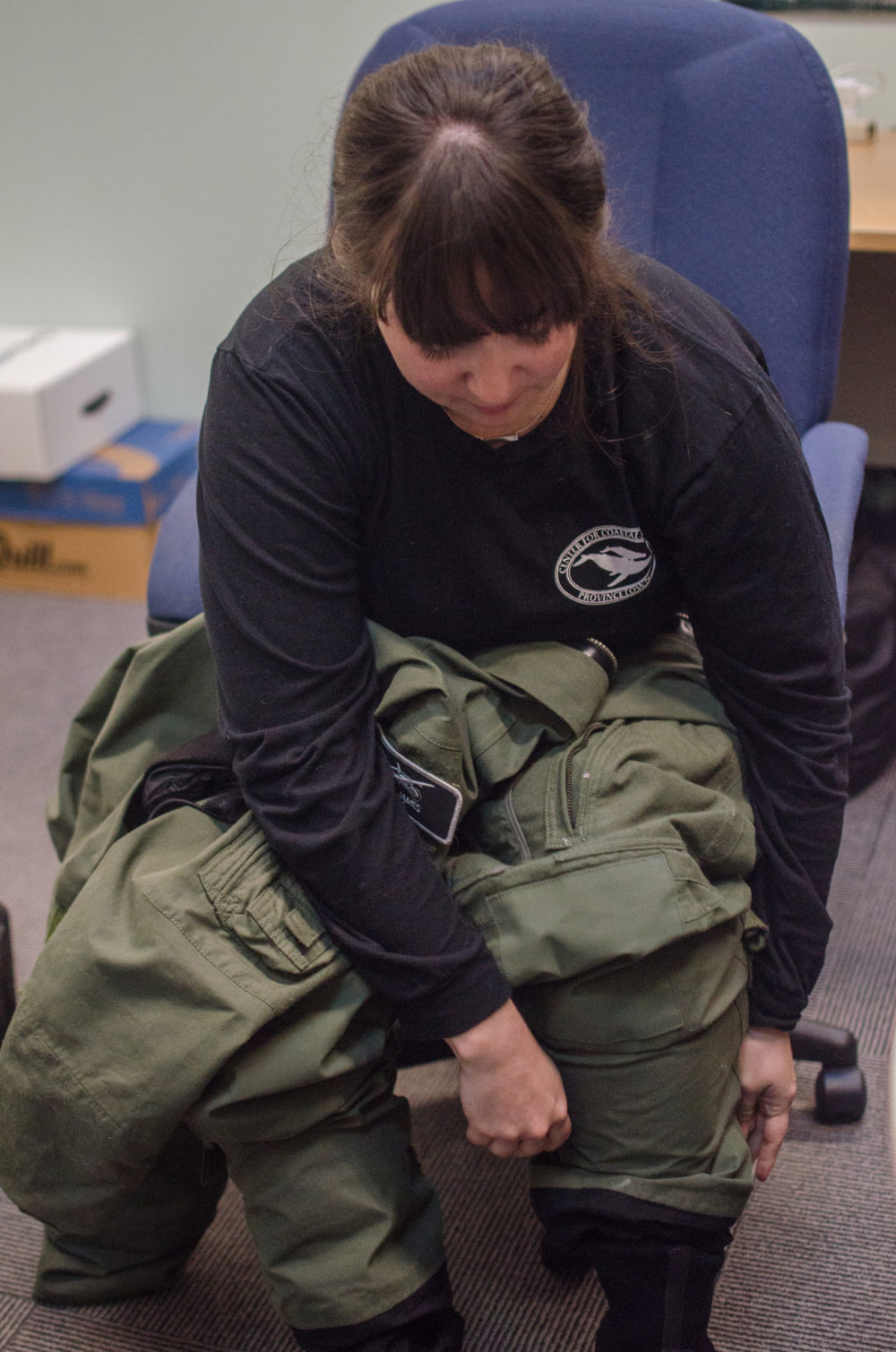 Amy James puts on her flight suit before a survey. (Sharon Brody/WBUR)
