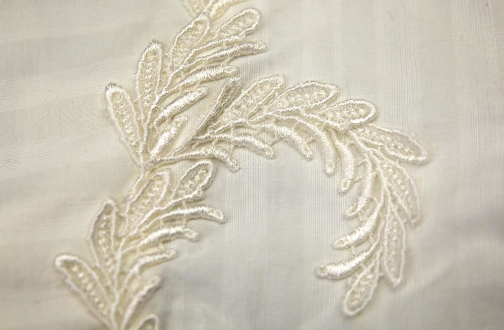 "A flower appliqué hides a seam on a white ""shirtwaist"" or blouse. (Robin Lubbock/WBUR)"
