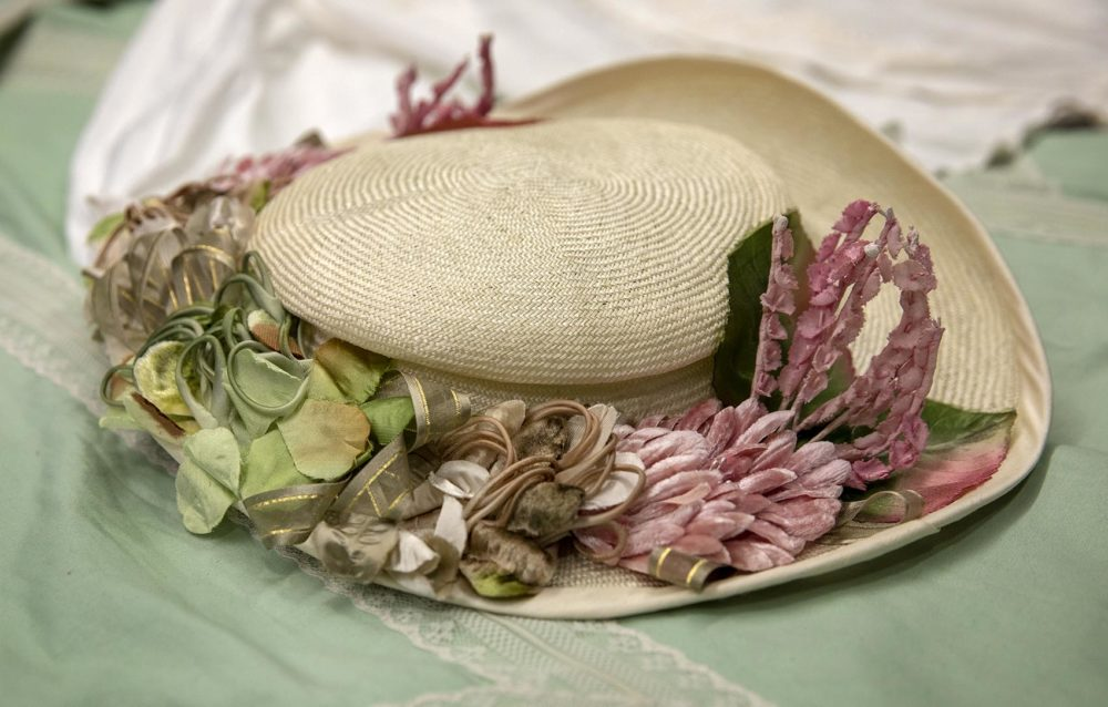 A parasisal straw hat trimmed with pink flowers, by Quinn Burgess. (Robin Lubbock/WBUR)