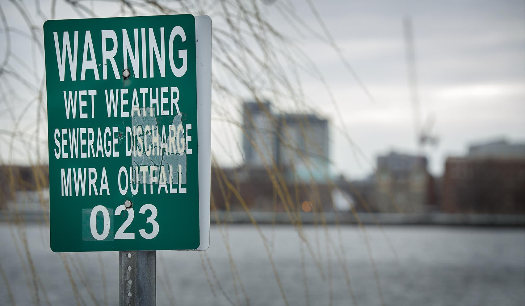 A MWRA wet weather sewage discharge outfall warning on the Charles River by the outlet of Boston's Muddy River (Robin Lubbock/WBUR)