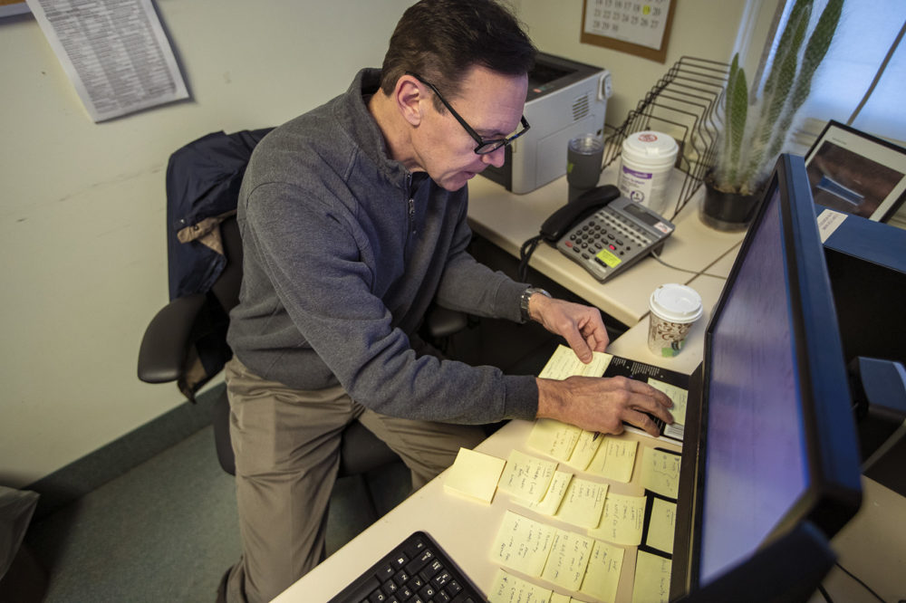 Army veteran Chris Riga rearranges Post-it Notes on his desk, which he uses to assist him in remembering tasks he has to do throughout the day at his job as patient experience coordinator at the VA in Northampton, Mass. (Jesse Costa/WBUR)