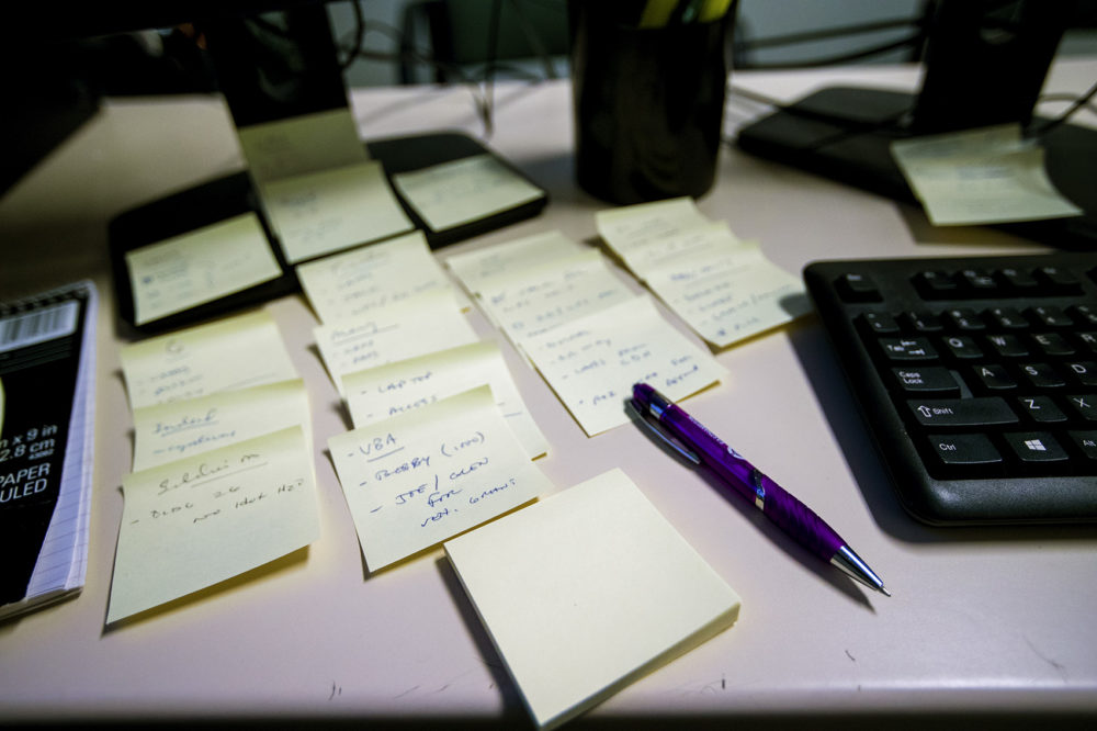 Sticky notes organized on Riga's desk. (Jesse Costa/WBUR)