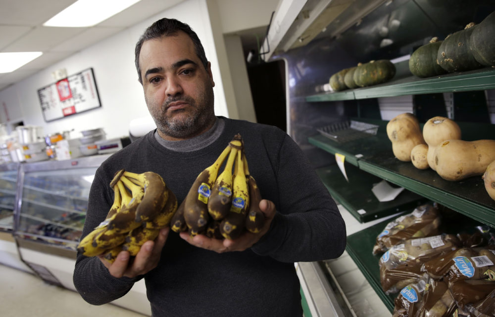 In this photo from Dec. 5, 2018, market owner Junior Hernandez holds up bananas, which are spoiling on his store shelves due to lack of customers in his neighborhood, in Lawrence, Mass. (Charles Krupa/AP)