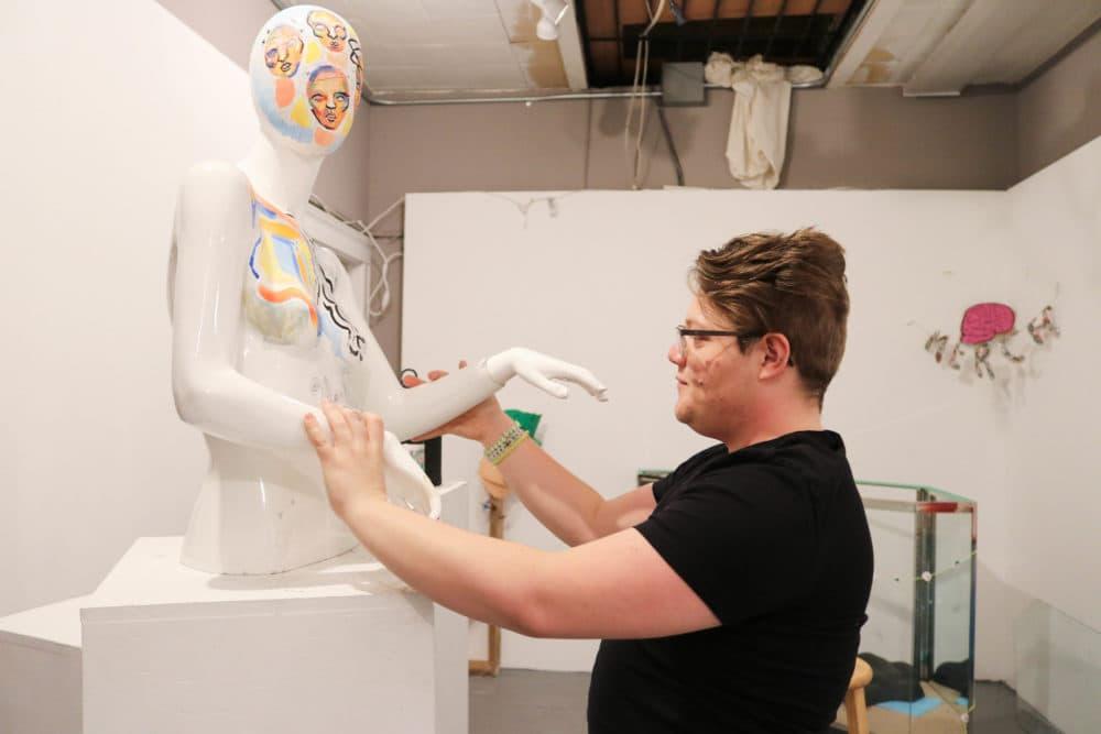 Kal Anderson adjusts a statue at Dorchester Art Project. (Olivia Deng for WBUR)