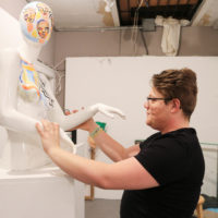 Kal Anderson adjusts a statue at Dorchester Art Project. (Olivia Deng for WBUR)