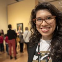 "Layla Bermeo, assistant curator of American paintings, at the ""Frida Kahlo and Arte Popular"" exhibition at the MFA. (Robin Lubbock/WBUR)"
