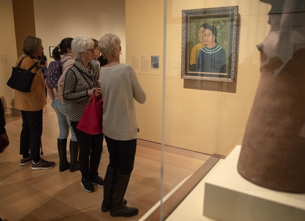 """Visitors at the MFA Boston look at Frida Kahlo's """"Dos Mujeres."""" (Robin Lubbock/WBUR)"""