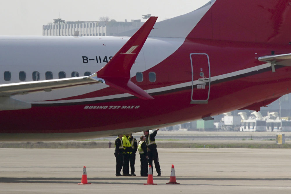 Ground crew chat near a Boeing 737 MAX 8 plane operated by Shanghai Airlines parked on tarmac at Hongqiao airport in Shanghai, China on Tuesday. (AP)